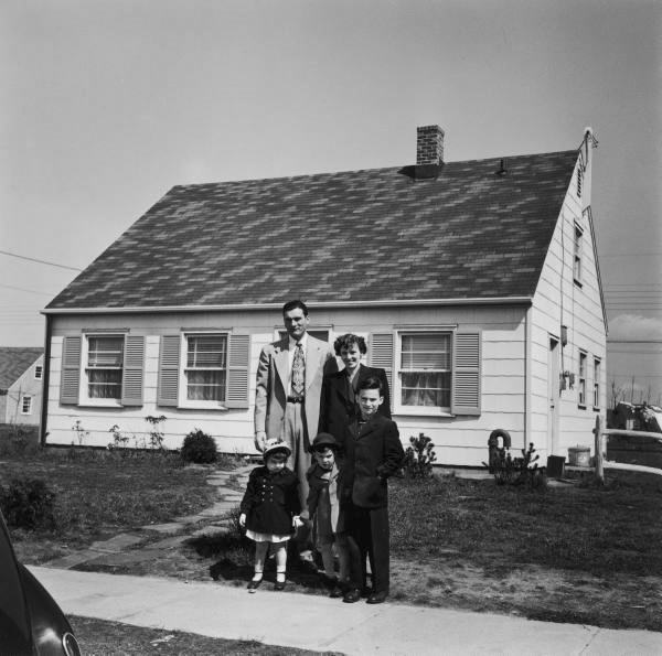 A family of 5 outside their newly purchased home in Levittown, NY. Now this house sells for $500,000.