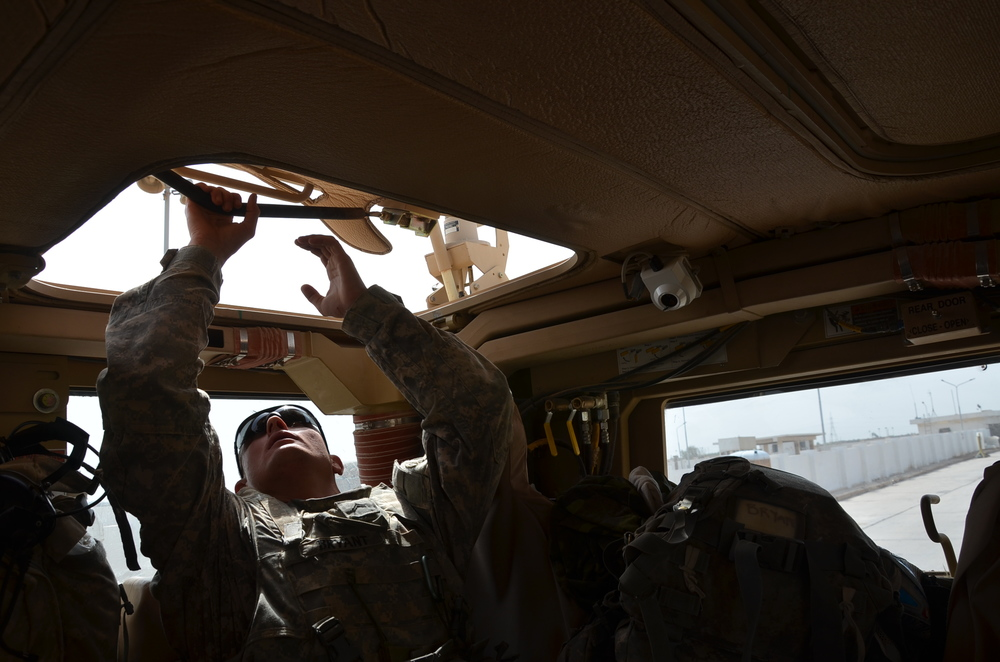Bravo Company's Cpl. Scott Bryant pops the hatch of an MRAP vehicle to get some air on the road march from Al-Asad Air Base in Anbar province to Camp Taji near Baghdad. Sept. 28, 2011. Photo by Dan Zak