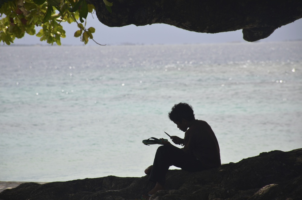 A boy on Ejit Island fixes his sandal.