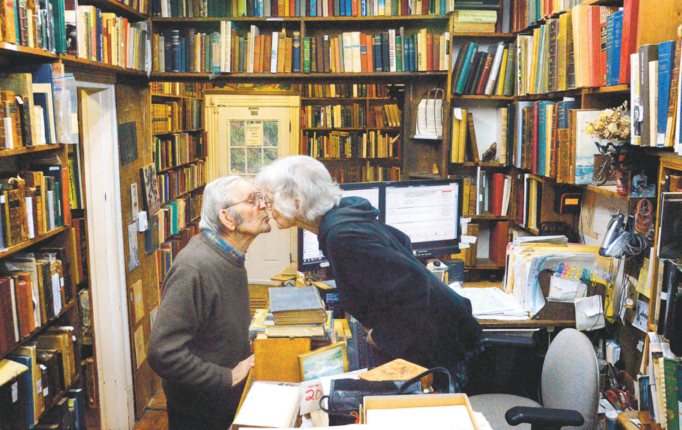 Edward Hughes, 91, kisses his wife, Natalie, 80, goodbye, top, after dropping her off at the Bookhouse; she runs the shop and he buys the books. (Photo by Dan Zak / The Washington Post)