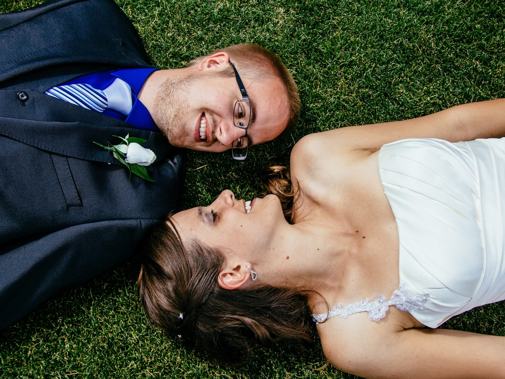 Wedding Photography. Bride and Groom lay in the grass staring into each others eyes.