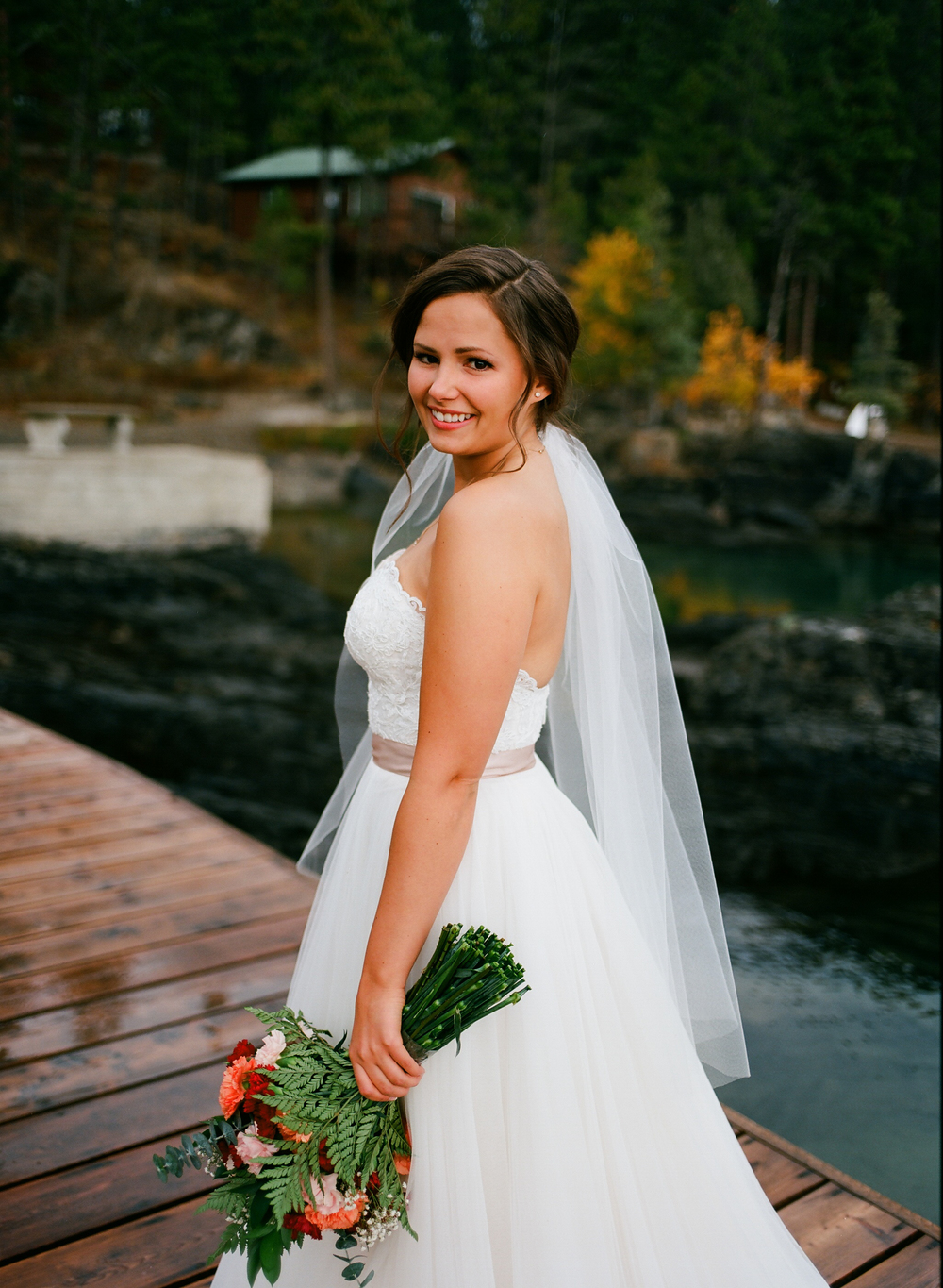 Wedding photography. Bride Brook waits for her groom on Flathead Lake, Montana