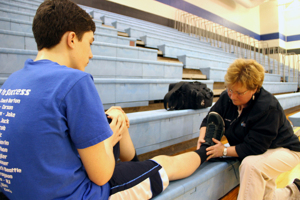 Kerry Waple, an athletic trainer, looks at the ankle of RJ Mehan in Worthington, Ohio