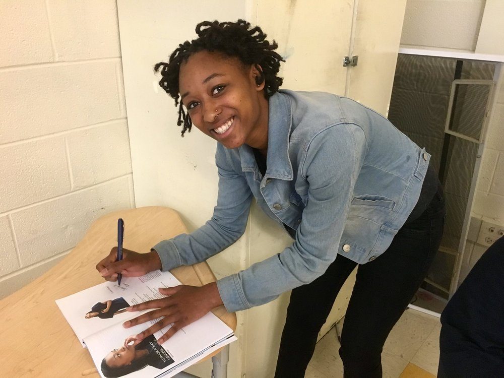 "Amira signs a copy of ""Our Lives Matter"""