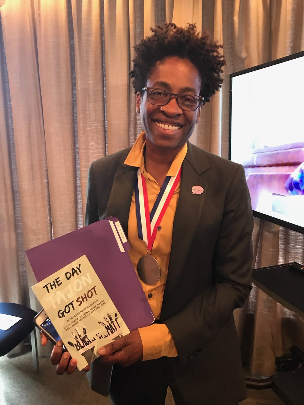 2018-2019 National Ambassador for Young People's Literature, Jacqueline Woodson, proudly displaying her copy of  The Day Tajon Got Shot