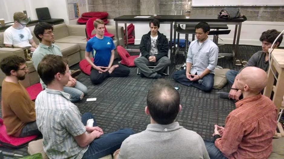 Michael Munson (in blue) meditates with other Hack Reactor students.