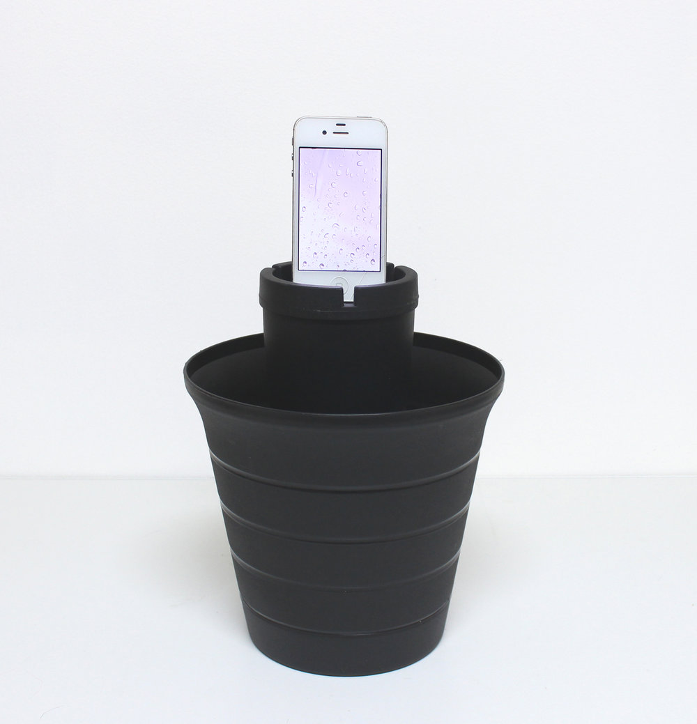 "Calming Rain for Meditation/Butt Bucket , 2017, iphone, continuous loop video with audio, ""butt bucket"" ashtray, planter, concrete, pigment,  foam, 15 x 8 x 8 inches"