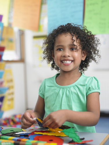 stock-photo-portrait-of-smiling-little-girl-assembling-puzzles-in-classroom-143878201.jpg