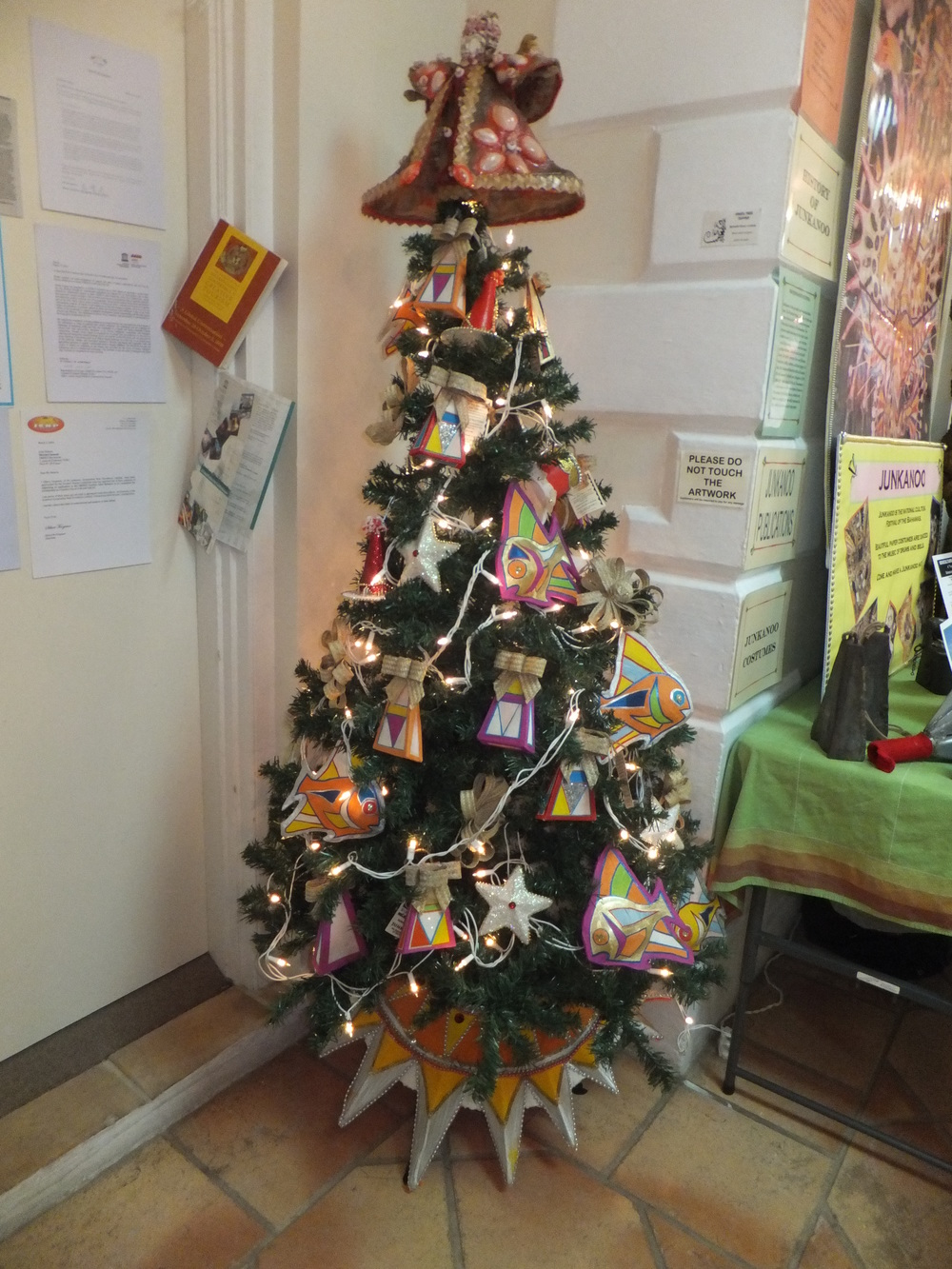 A uniquely Bahamian Christmas tree decorated with hand made junkanoo ornaments and a straw and shell studded tree topper angel