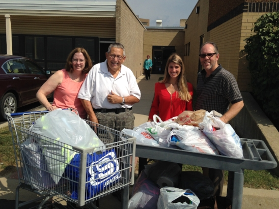 PICTURED ABOVE: Deacon Patrick and his wife Nancy dropping off school supplies from a past year!  Let's see if we can collect even MORE this year.