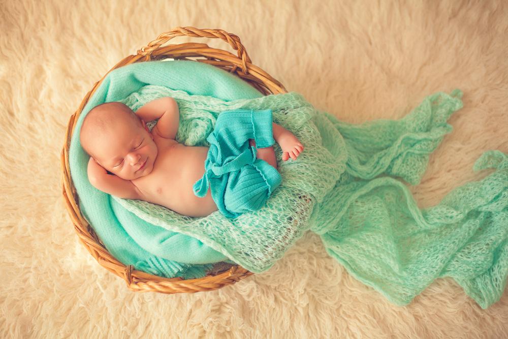 baby boy sleeping in a basket
