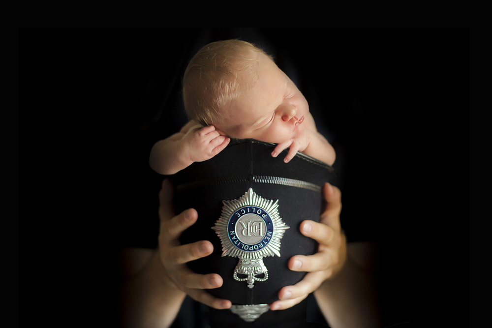 newborn baby in policeman hat