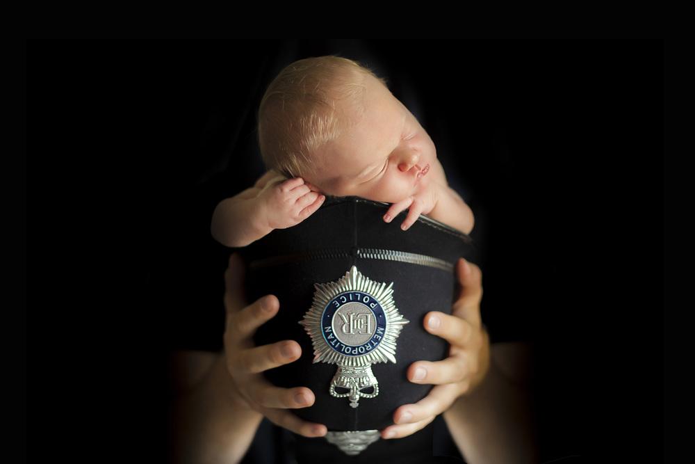 newborn baby in policeman hat