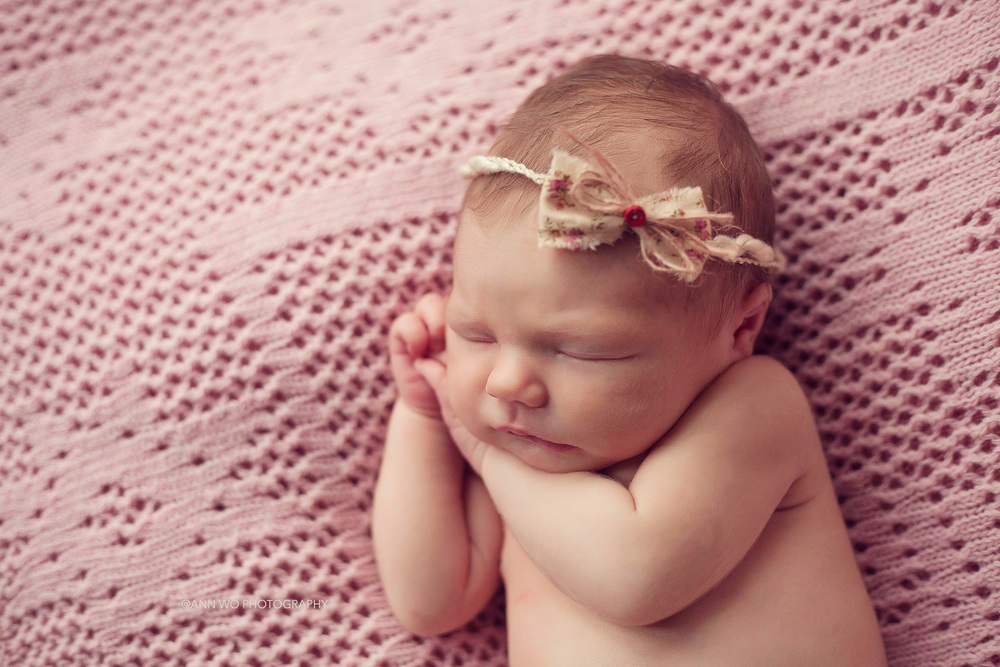 newborn baby girl wearing little bow