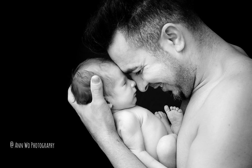 father and newborn baby black and white skin to skin photo