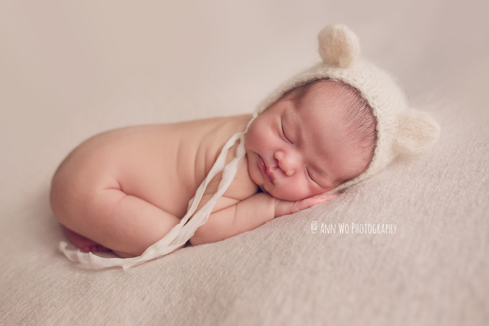 newborn photographer London Ann Wo cream posing fabric white bear hat