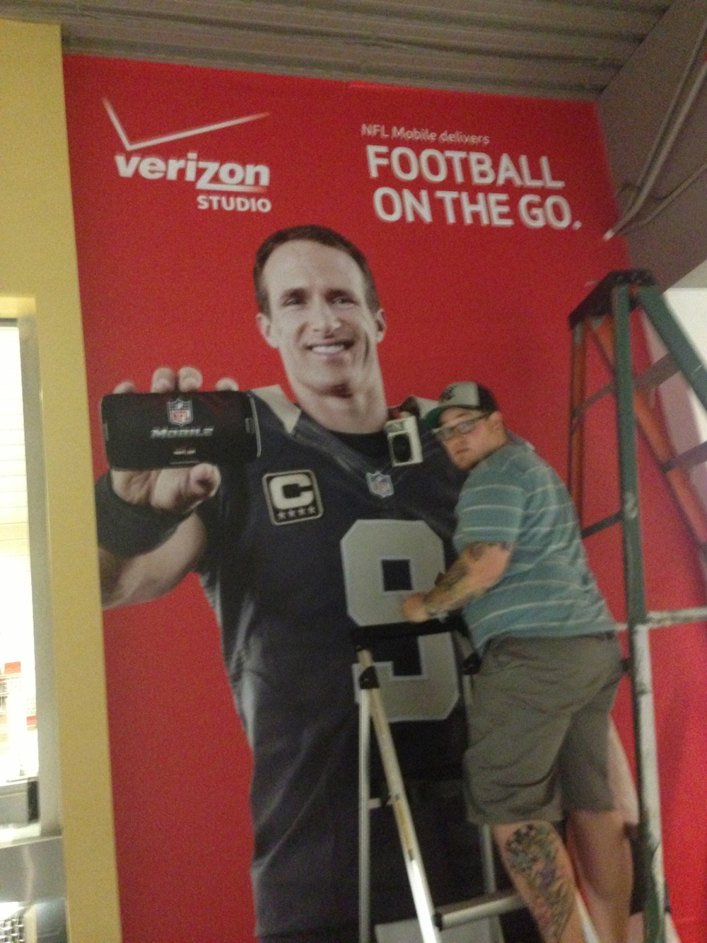 Brent puts the finishing touch on a wall graphic install for Verizon at the Mercedes Benz Superdome