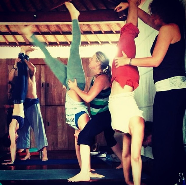 @danallopez practicing headstands in bali wearing a custom airbrushed & cut OM tee