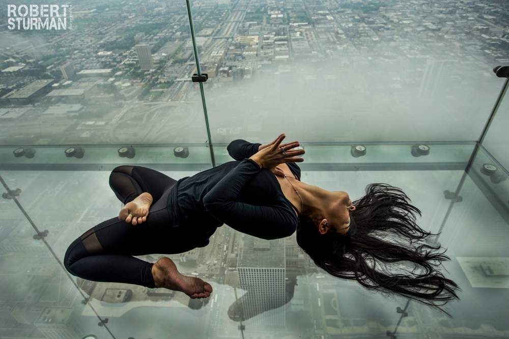 71)   Izabel Olson- The Chicago Skydeck Ledge --- 103 Stories High. At 1,353 feet up, The Ledge's glass boxes extend out 4.3 feet from the skyscraper's Skydeck on the 103rd floor. The tower is a world-renowned building, a Chicago icon. The eighth-tallest building in the world, it remains the tallest building in the Western Hemisphere, standing 1,450 feet and 110 stories tall.