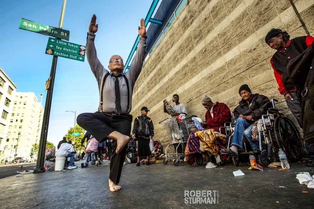 "49) Yoga and survival on Skid Row: Los Angeles, California  Yoga is not a subculture limited to a small percentage of humanity. It has and continues to rapidly grow into a cultural tool for sanity and survival, easily accessible wherever it can be learned — from prison cells to refugee camps. All it takes is learning and so many yogis in this world are hopping on the Seva Train and sharing what we can.    Seva is a word worth defining and remembering again and again: ""Seva"" is a Sanskrit word meaning ""selfless service"" or work performed without any thought of reward or repayment. In ancient India seva was believed to help one's spiritual growth and at the same time contribute to the improvement of a community.   Pictured: Eduardo Alvarado who recently completed his 200 hour teacher training and is bringing yoga to the mission on Skid Row, where he lives. There were hundreds of people camped in the streets. Yoga has become one of Eduardo's greatest tools for survival, sanity and creating change."