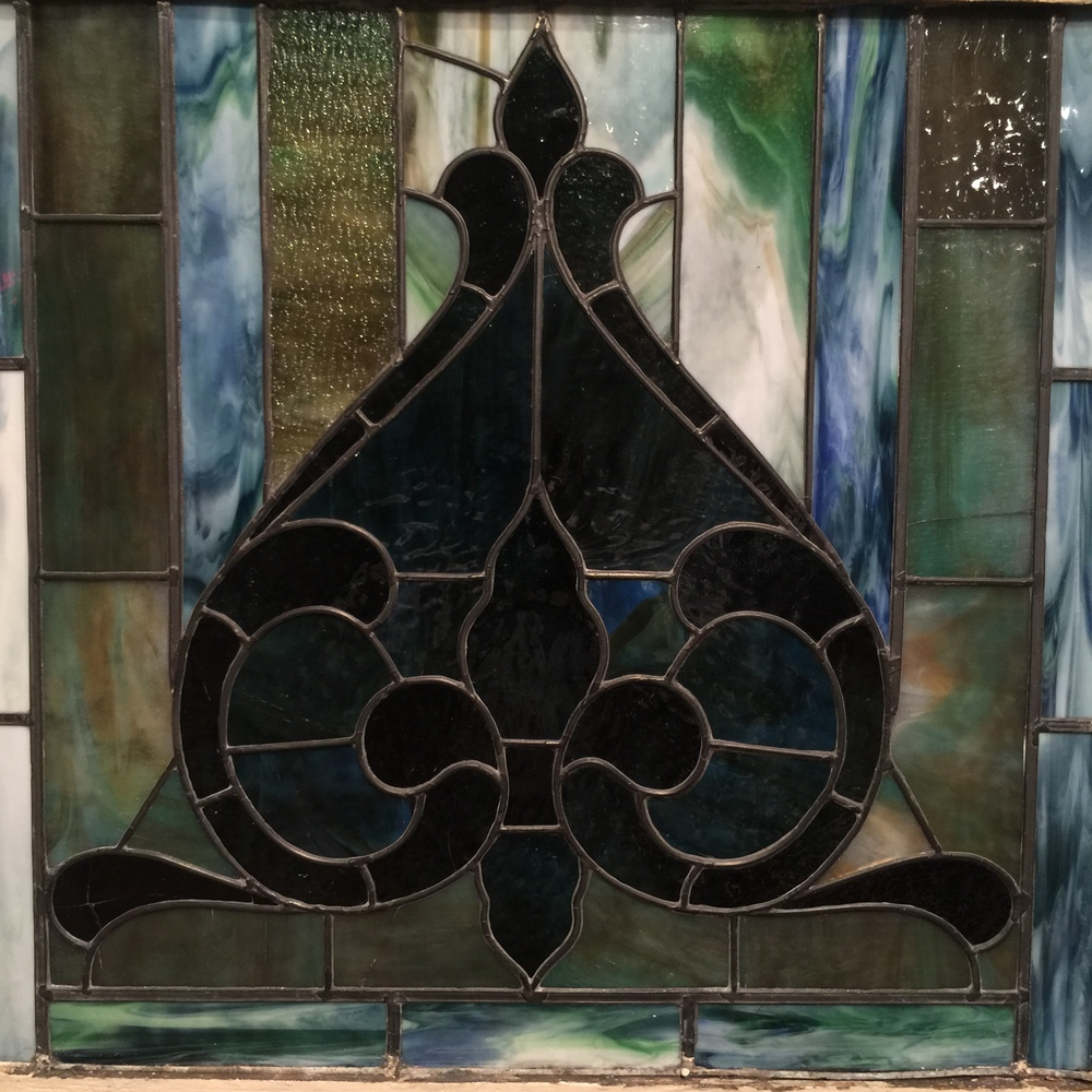 Stained glass window on loan from First United Methodist Church. This rendition of a blue flower hung in the Methodist church building after the American Civil War.