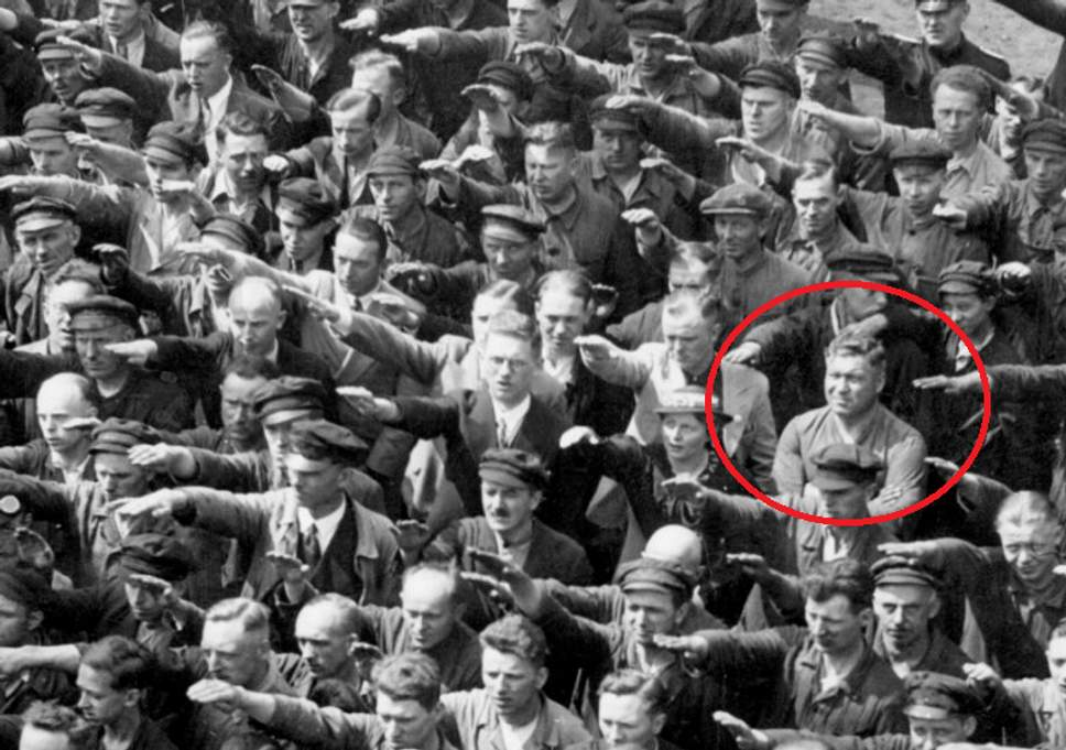 August Landmesser refuses to salute, though it is mandatory under German law at this time in 1936. Landmesser was originally a member of the Nazi party since 1931. However, he fell in love with a Jewish woman and proposed to her in 1935. When he was discovered, he was expelled from the Nazi party. He, his pregnant wife, and his daughter were later sent to concentration camps.