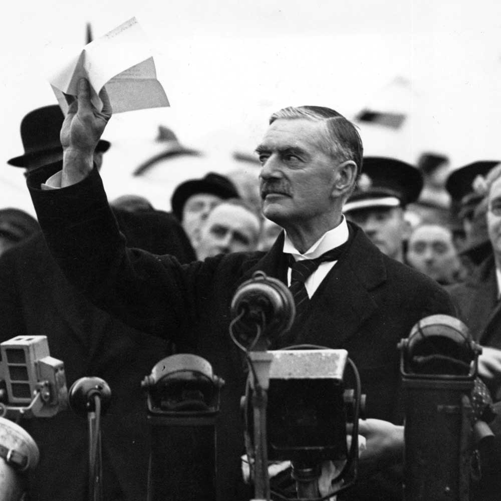 "Neville Chamberlain waving the Munich Agreement, declaring he had achieved ""peace in our time,"" 1938."