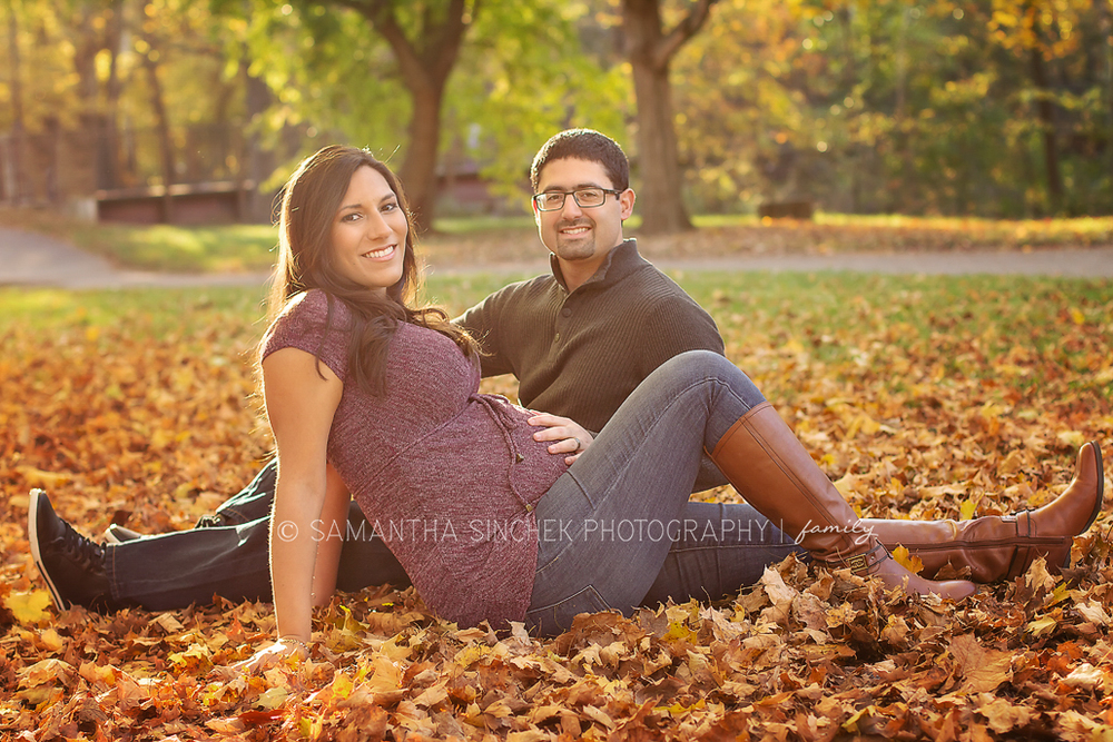 parents to be sit in the fall leaves at a maternity session at sharon woods ohio