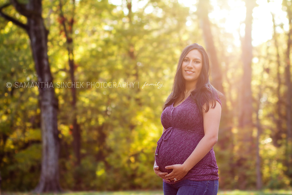 mother to be stands bathed in sunlight at cincinnati maternity session