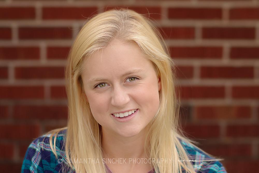 senior girl smiling in front of brick building at sharon woods in cincinnati ohio