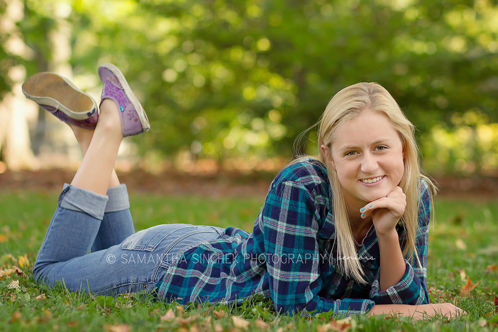 high school senior posing by laying on ground at sharon woods in cincinnati ohio