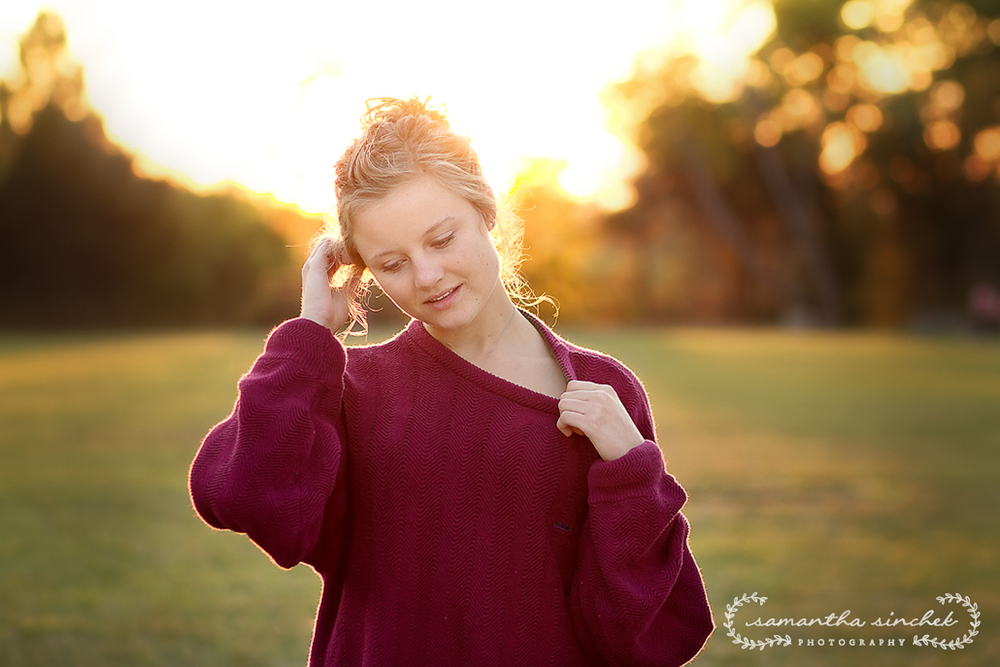 high school senior standing in field with sun behind her