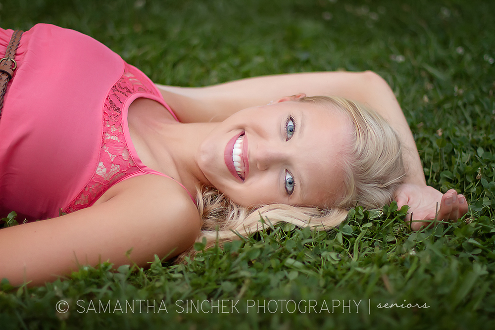 girl lying in grass during senior portrait session at ault park in cincinnati ohio