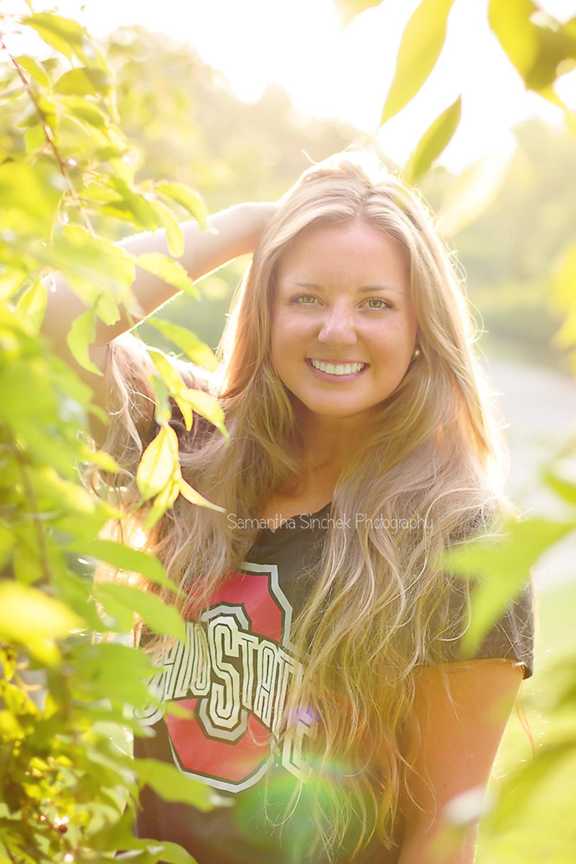 alyssa stands in the foliage at ault park in CINCINNATI ohio for senior pics