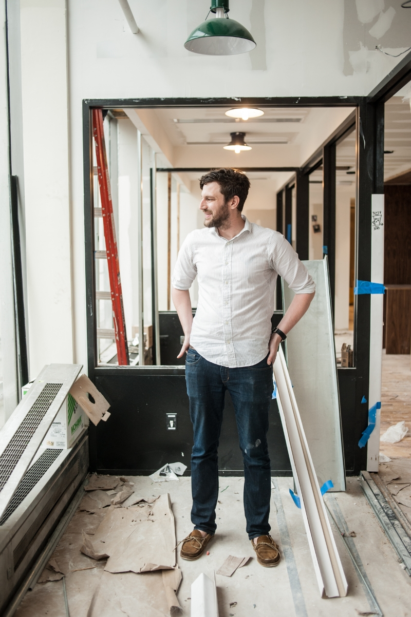 Devin Vermeulen WeWork Creative Director standing inside the Fulton NY location during construction.