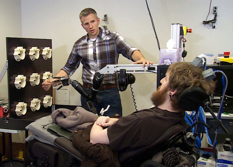 Robert Gaunt tests Nathan Copeland's ability to detect touch by tapping fingers on a robotic hand.  UPMC/Pitt Health Sciences