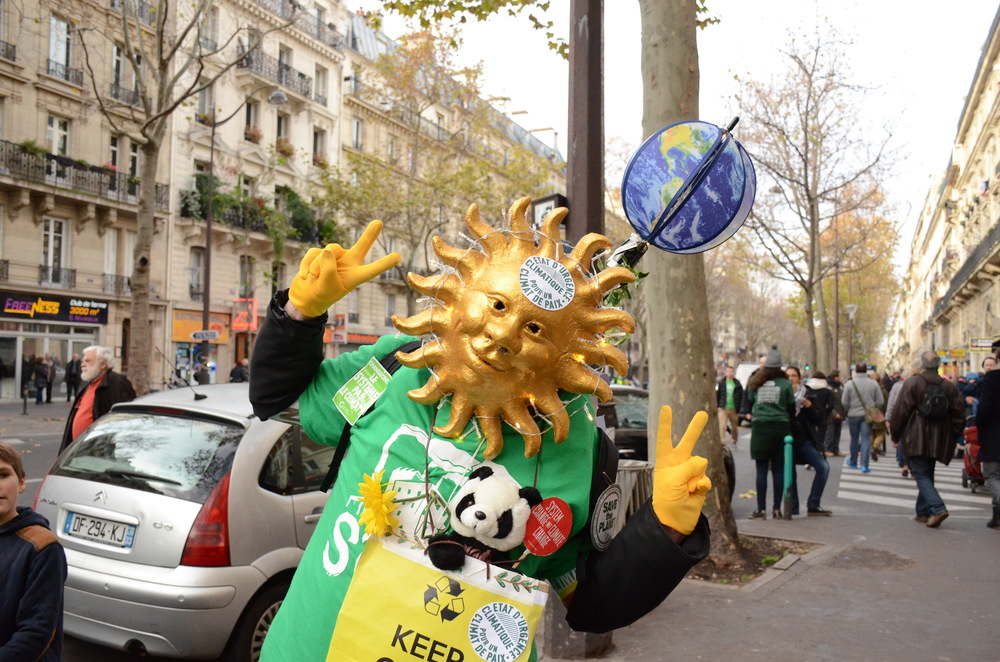 A demonstrator sports a costume with an environmental message as he walks along Boulevard Voltaire.