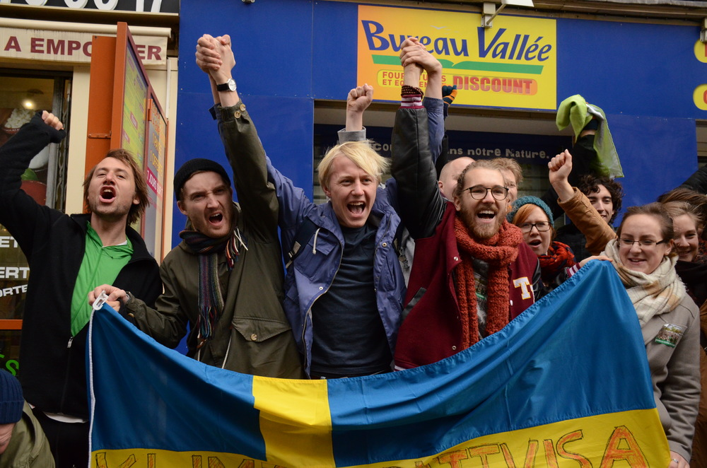 Climate activists, holding the Swedish flag, clasp hands in single file solidarity.