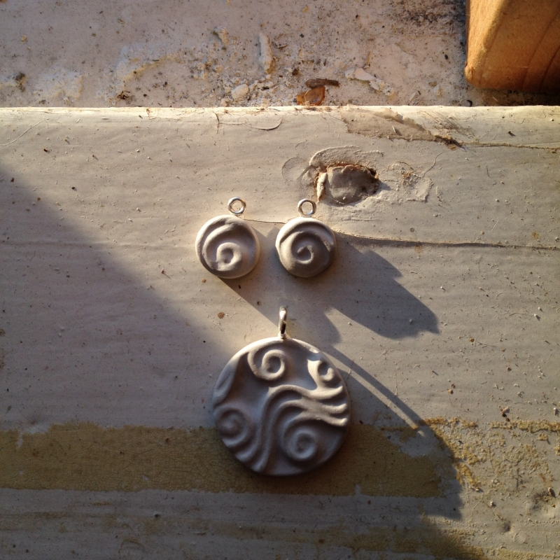 Doodle pendant and earrings, before firing. These pure silver pieces are created with a material called PMC (precious metal clay) which is a man-made clay made up of finely ground particles of silver in an organic binder. The pieces you see here were fired in a kiln at 1650 degrees farenheight. All the binder material burns off and you're left with pure silver.