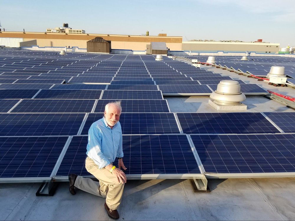 (CUNY Solar Ombudsman Ron Reisman, in front of a community solar array to which he is a subscriber.)