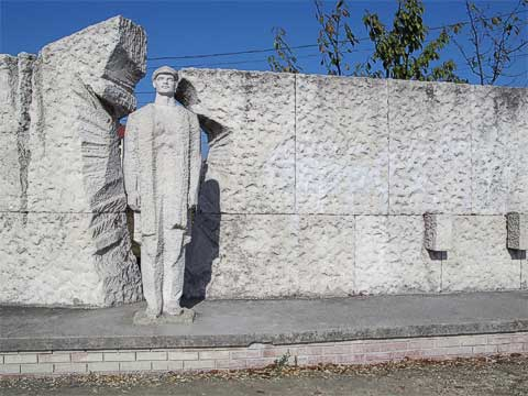 This sculpture is a liberation monument, representing a worker breaking through the wall.