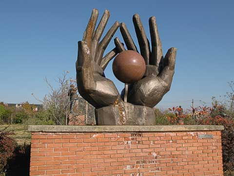 There used to be a red star on the sphere of this statue. The sphere represents the ideals of communism, and the hands are protecting it while also holding it out for others to appreciate.