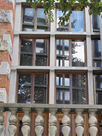 The library is on a block which is not square; the building's exterior matches the block, but the reading room inside is squared off. To pull this off, Plečnik used double windows on the outside of the room; the river wall's windows are parallel (just to the left of the middle of the picture), but the other side's windows are not (as you can just make out in the second picture).