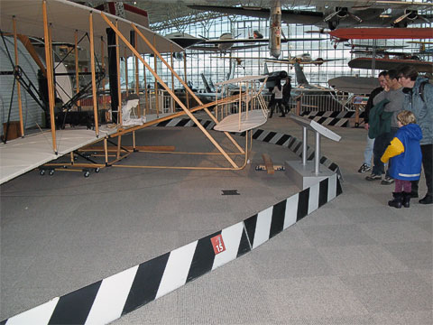 Melody and Kenny look at a reproduction of the original Wright Flyer.