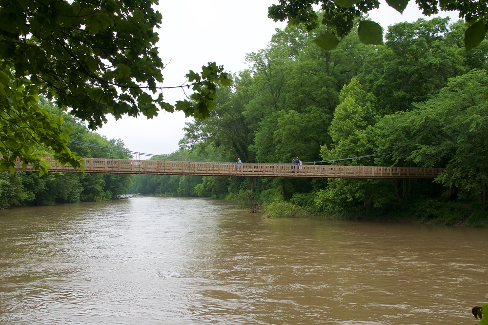 Pedestrian suspension bridge over Sugar Creek, which was overflowing