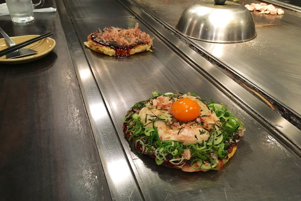 My pork and yam okonomiyaki (with green onions and egg) in front, Melody's squid one in back; they both have sauce and katsuobushi (bonito flakes)