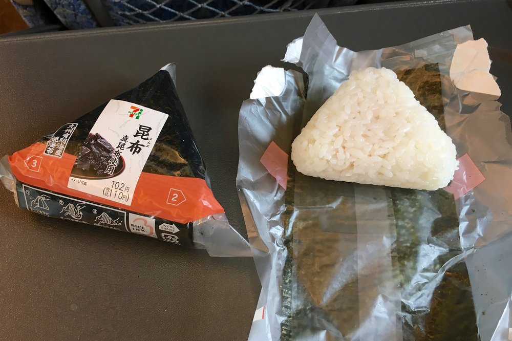 Onigiri, one in original packaging and one ready to have its nori removed and wrapped around the rice