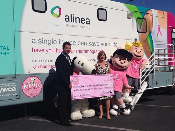 Komen OC's Executive Director, Lisa Wolter, receiving a check from Snoopy & Jason Soyster, Knott's Berry Farm's Communication's Manager.