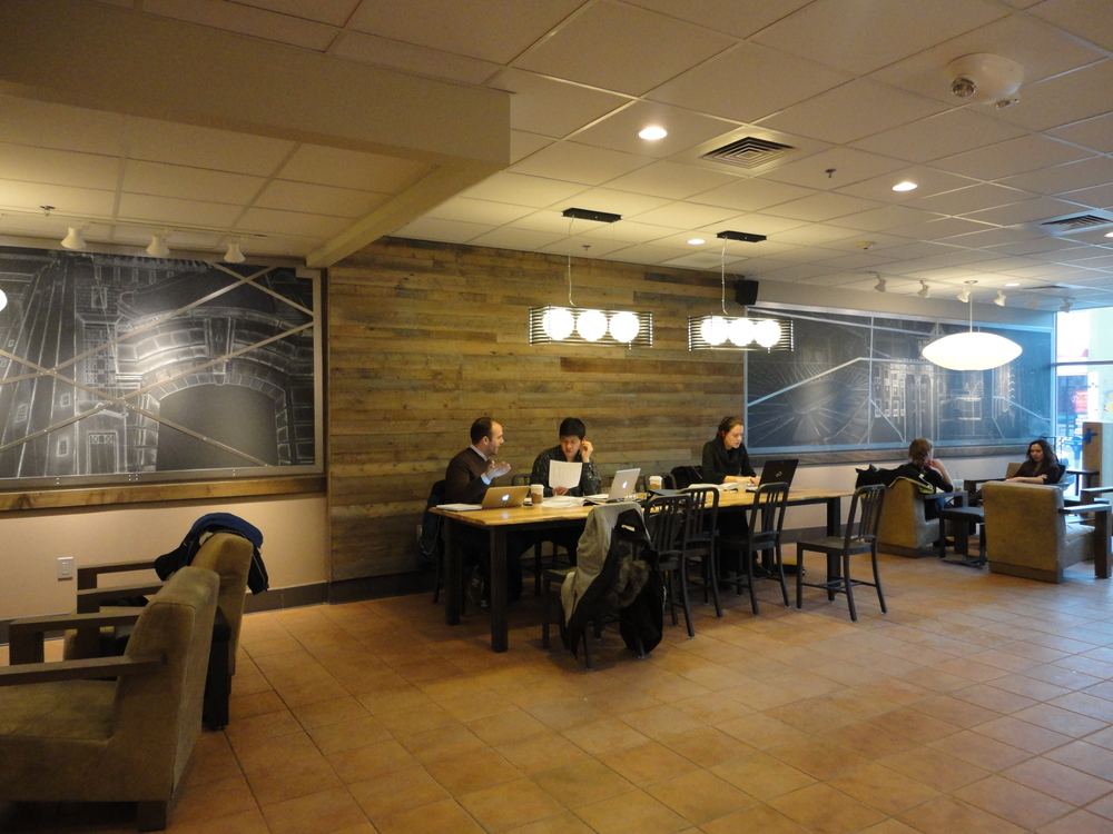 Chalk mural with steel border located at the East University Starbucks.  The mural on the left depicts prominent campus landmarks with the overlapping steel sections creating an aerial map of the Diag.  The mural on the right depicts popular city locations with the overlapping steel creating an aerial map of the main streets of downtown Ann Arbor.  A star can be found that indicates the location of the Starbucks on the map