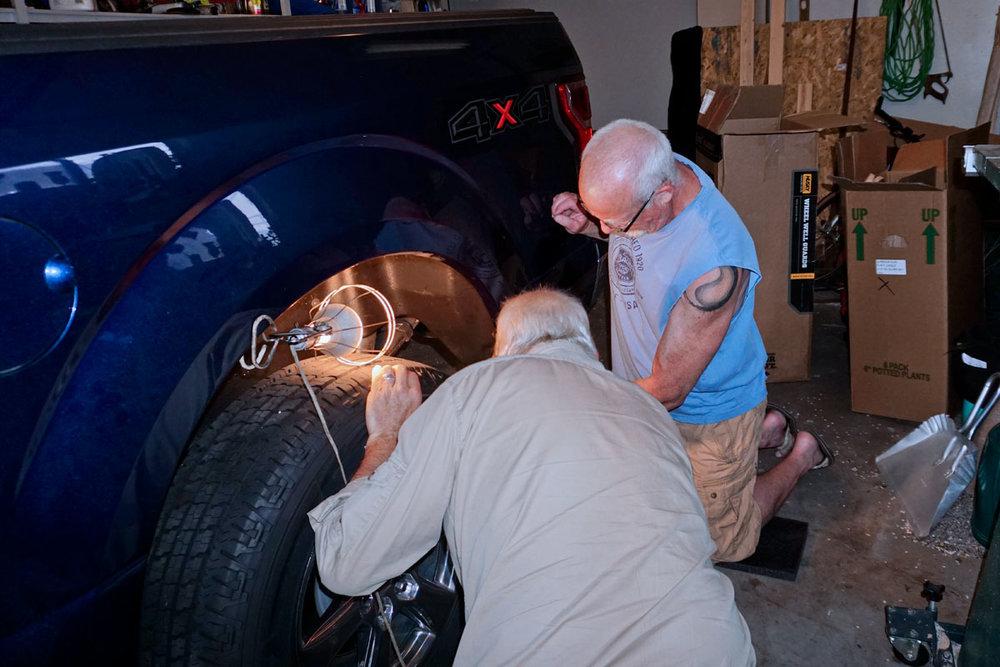© 2018 Louise Levergneux. Marty and Michael installing the new mudflaps on the F-150. /  Marty et Michael installant les nouveaux pare-boue sur le F-150.